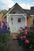 Tiny, white gazebo with bench in flowering garden with purple delphiniums