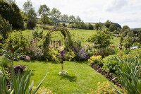 Summer garden with herbaceous borders and vegetable beds in rural surroundings