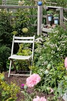 Wooden folding chair in flowering garden against simple wooden fence