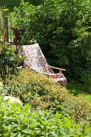 Blanket on wooden armchair in summer garden