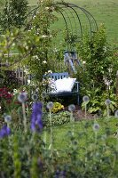 Idyllic seating area; white cushions on blue garden bench under trellis arbour in summer garden
