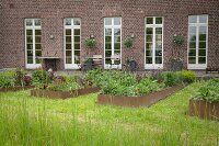 Raised beds with metal surrounds outside renovated, brick farmhouse