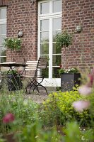 View from garden to seating area with folding chairs and table outside brick farmhouse with white, lattice French doors