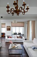 Bright, open-plan interior with chandelier in front of purist coffee table and white sofas