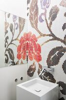 Floral mosaic reflected in mirror to one side behind cubist sink with designer, wall-mounted taps