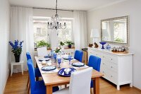 Dining room furnished in white with bold accents of magenta and royal blue