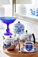 Chrome teapots and blue and white crockery on wooden tray in front of blue glass goblet