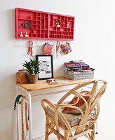 Rattan chair at small table below red type case holding jewellery and small, Oriental bags