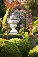 Antique, stone Greek urn in landscaped garden with low box hedges and old wrought iron gate in background