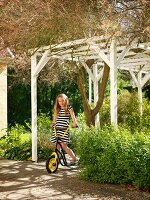 Girl on scooter under white pergola in summer garden