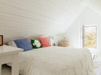 Rustic, white, attic bedroom with crocheted bedspread and open window