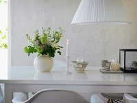 Romantic arrangement of lit candle and vase of flowers on glossy white table