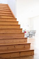Simple wooden staircase with view of armchair in living room to one side