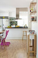 Folding table against wall and dining area in open-plan kitchen with worksurface below stainless steel extractor hood