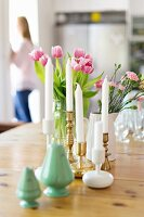 Green salt shakers, white candles in brass and ceramic candlesticks and vases of spring flowers on wooden table