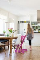 Woman walking past classic shell chairs and pink Tripp Trapp chair at wooden table in modern kitchen