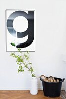 Framed, typographic poster of letter G on wall above leafy branch in white vase and bucket of logs on floor