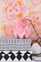 Storage boxes with black and white geometric patterns and table lamp with pink, origami paper lampshade against wall with retro floral wallpaper