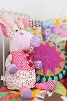 Soft toy made from fabric remnants and scatter cushions on bed