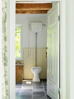 Open door showing view of toilet on grey tiled floor in rustic bathroom