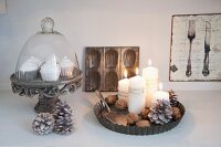 Lit pillar candles, fir cones and nuts in flan tin next to muffin ornaments on vintage cake stand