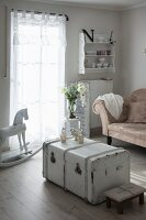 White vintage trunk, rocking horse and antique sofa in vintage-style living room