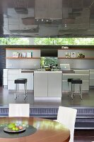 Elegant fitted kitchen on raised platform with ribbon window and reflective metal ceiling