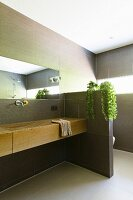 Modern tiled bathroom with elegant wooden washstand and partition screening toilet