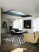 Black leather armchair and sofa around coffee table on black and white patterned rug in living room with skylight