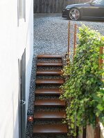 Minimalist external staircase with rusty metal treads; car on gravel drive in background