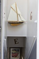 Model sailing boat above head of staircase in narrow stairwell