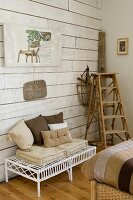 White wicker bench with cushions in various shades of brown next to vintage wooden ladder against white wood-clad wall