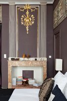 Disused marble fireplace below gilt stucco element on wall in corner of living room