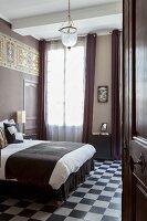 View of double bed and chequered floor in elegant bedroom seen through open door