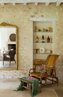 Wicker chair and footstool in front of glass shelves in niche in stone wall next to gilt-framed mirror