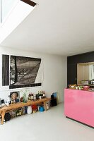 Bottles on wooden bench below drawing on wall and kitchen counter with pink front to one side