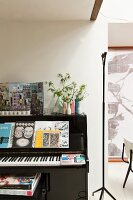Black upright piano next to minimalist standard lamp with black metal frame
