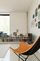 Butterfly chair with pale brown leather cover in front of half-height fitted bookshelves