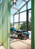 Blue motorbike behind green partition in greenhouse