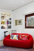 Red designer couch with patterned scatter cushions in corner of living room with white partition