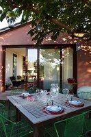 Set garden table below deciduous tree in front of open glass door in gable-end façade