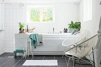 White, retro cord chairs next to bathtub below window and open shower area in modern, white bathroom