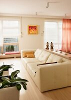 Cream leather sofa and potted orchids without flower spikes; windows with Roman blinds in background