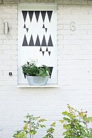 Planter on metal shelf with graphic pattern on whitewashed brick façade