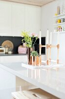White candles in candelabra and flowers and succulent in copper-coloured containers on white-painted counter in modern kitchen