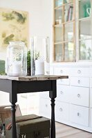 Tall glass candle lanterns on rustic table with black-painted frame