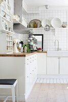 White, fitted kitchen cupboards on tiled wall