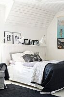 Double bed with black and white bedspread in attic room with wood-clad sloping ceiling