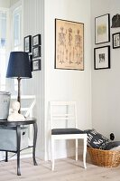White-painted chair with black seat cushion below framed pictures in corner