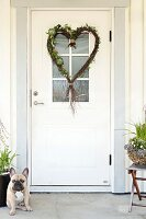 Heart-shaped wreath made from birch twigs hanging on white front door